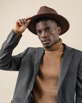 Giovane uomo bello che posa con il cappello