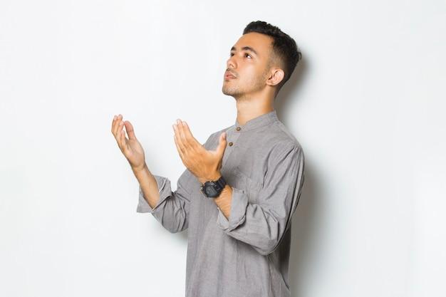 白い背景で隔離の祈りの若いハンサムな男