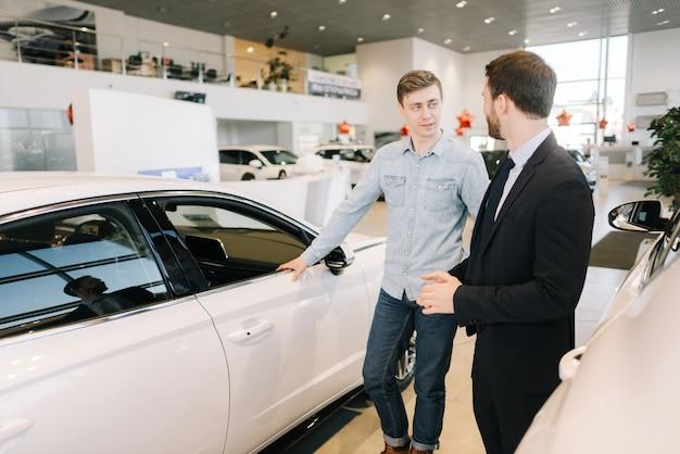 Молодой красавец готовится купить новую машину в автосалоне