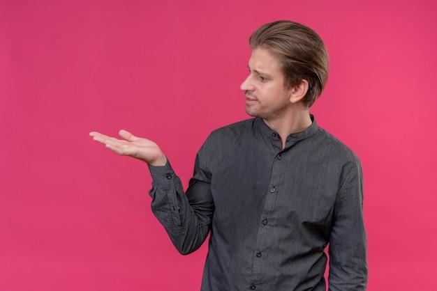 ピンクの壁の上に立っている彼の手の腕でコピースペースを提示する若いハンサムな男