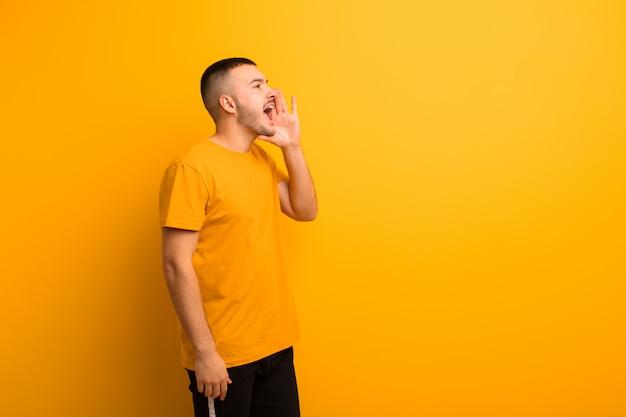 若いハンサムな男の縦断ビュー、幸せそうに見えて興奮している、叫び、平らな壁の側にスペースをコピーすることを求める