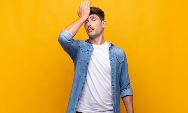 Young handsome man raising palm to forehead thinking oops, after making a stupid mistake or remembering, feeling dumb