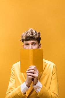 Young handsome man reading a book in a yellow scene