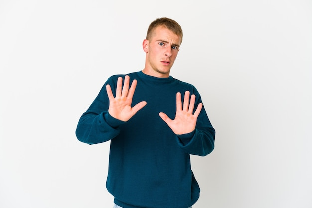 Young handsome man rejecting someone showing a gesture of disgust