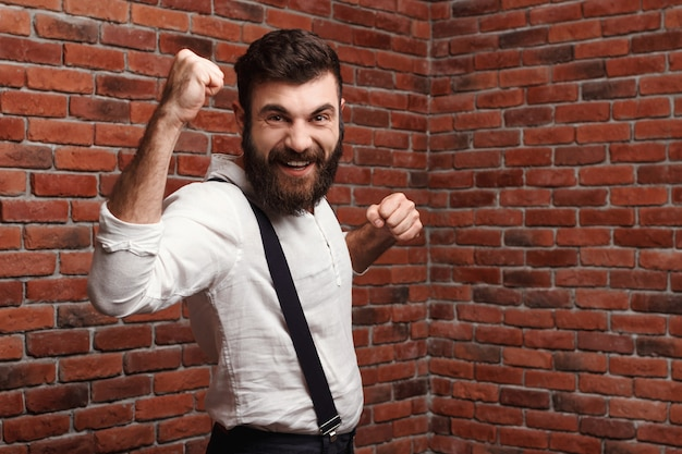 Young handsome man rejoicing posing on brick wall.