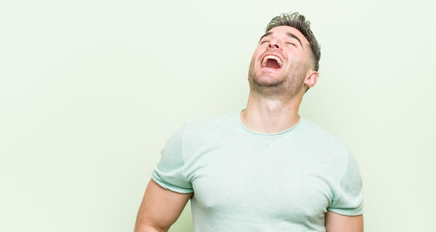 Young handsome man relaxed and happy laughing, neck stretched showing teeth.