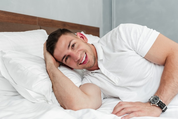 Young handsome man relaxing on bed after a tough day at work