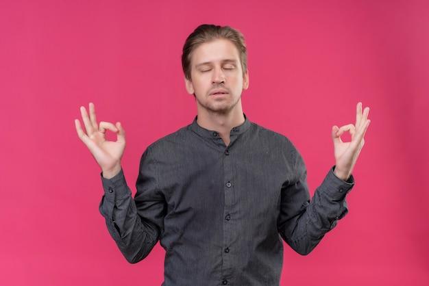 瞑想のジェスチャーを作る目を閉じてリラックスした若いハンサムな男