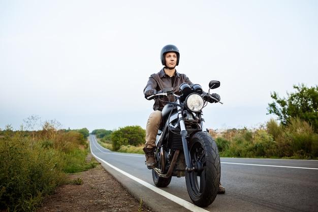 Молодой красавец, езда на мотоцикле на сельской дороге.