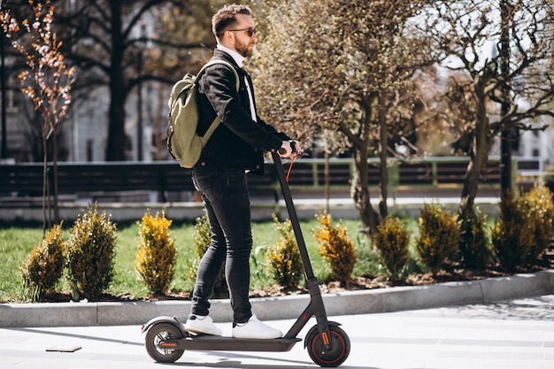 Молодой красавец катается на скутере в парке
