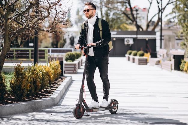Giovane uomo bello che guida su scooter nel parco