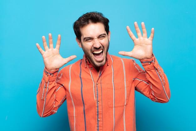 Молодой красивый мужчина кричит от паники или гнева, шокирован, испуган или разъярен, положив руки на голову