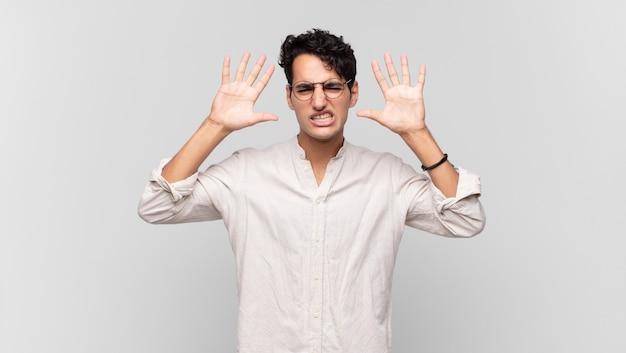 Молодой красивый мужчина кричит в панике или гневе, шокирован, испуган или разъярен, с руками рядом с головой
