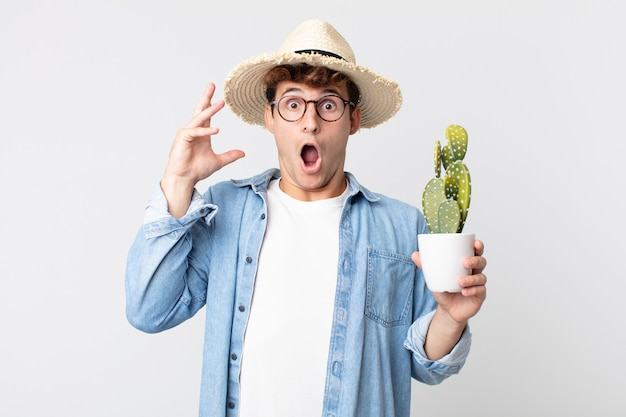 Young handsome man screaming with hands up in the air. farmer holding a decorative cactus