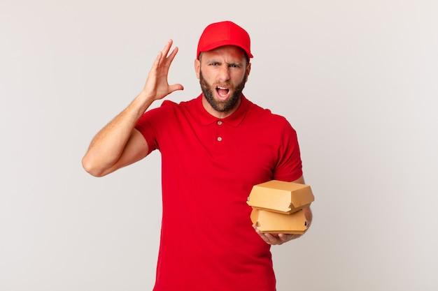 Молодой красавец кричит с поднятыми руками в воздухе концепции доставки гамбургеров