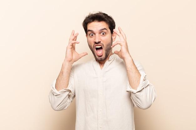 Молодой красивый мужчина кричит с поднятыми руками, чувствуя ярость, разочарование, стресс и расстройство