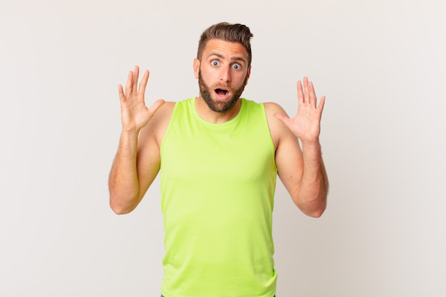 Молодой красавец кричит с поднятыми руками. фитнес-концепция