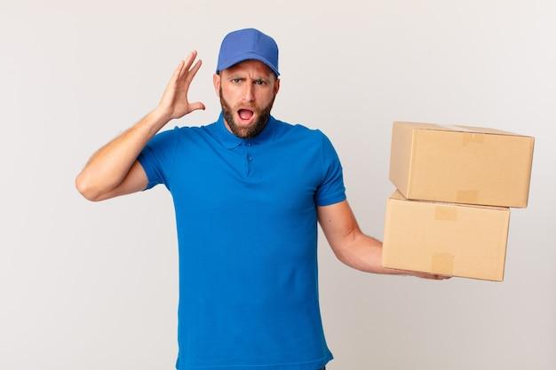 Молодой красавец кричит с поднятыми руками. концепция доставки пакетов
