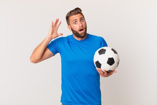 空中で手を上げて叫んでいる若いハンサムな男。サッカーのコンセプト