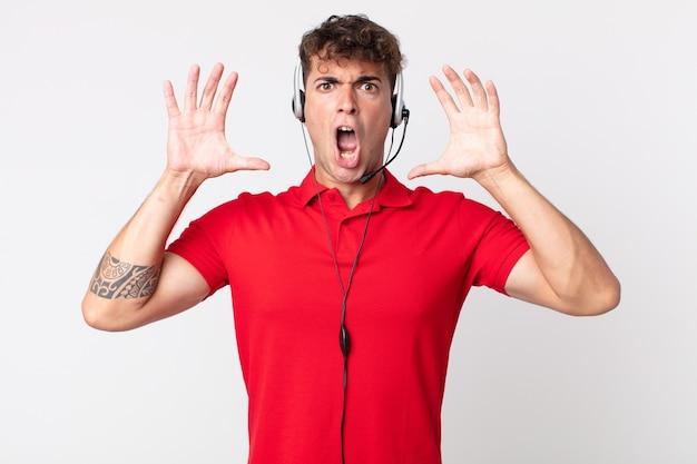 空中で手を上げて叫んでいる若いハンサムな男。テレマーケティングの概念