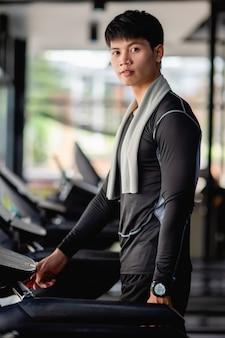 現代のジムのトラックで健康的なトレーニングのために実行されている若いハンサムな男の設定プログラム、