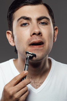 Young handsome man shaving on grey