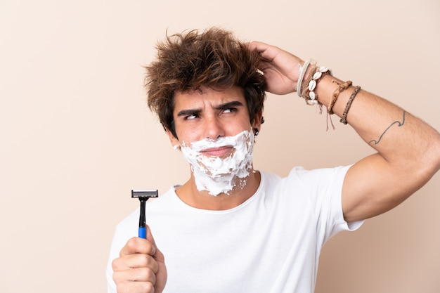 Young handsome man shaving his beard having doubts and with confuse face expression