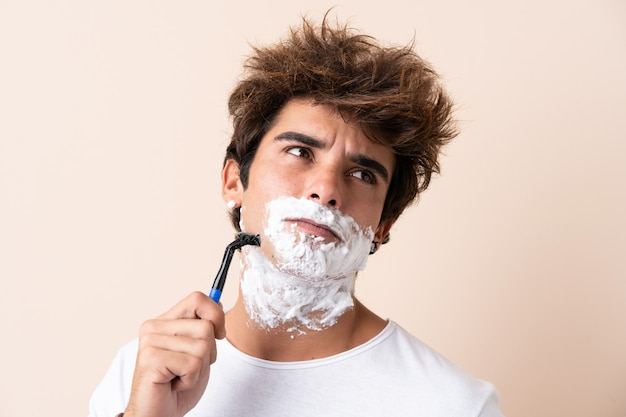 Young handsome man shaving his beard