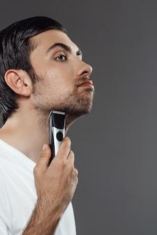 灰色の壁を剃る若いハンサムな男。
