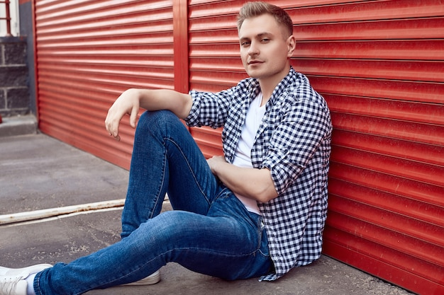 Young handsome man in a shirt and jeans near the red gate