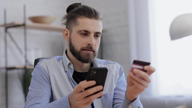Молодой красавец, делающий покупки в интернете, держа кредитную карту, сидя дома