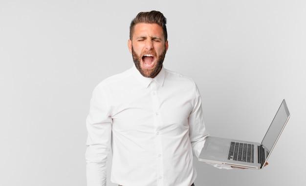 積極的に叫び、非常に怒っているように見え、ラップトップを持っている若いハンサムな男