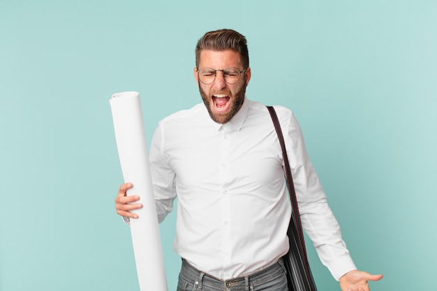 非常に怒っているように見えて、積極的に叫んでいる若いハンサムな男。建築家の概念
