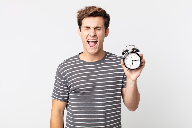 Young handsome man shouting aggressively, looking very angry and holding an alarm clock