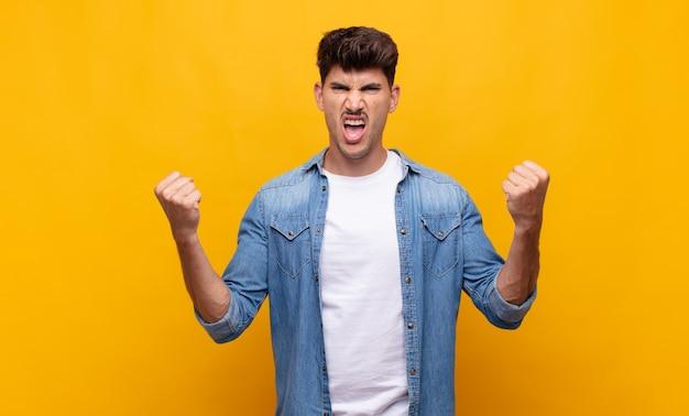 Молодой красивый мужчина агрессивно кричит с сердитым выражением лица или со сжатыми кулаками, празднуя успех