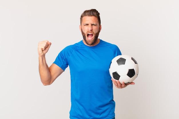Молодой красавец кричит агрессивно с сердитым выражением лица. футбольная концепция