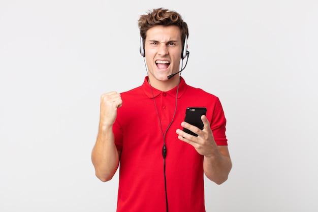 スマートフォンとヘッドセットで怒った表情で積極的に叫ぶ若いハンサムな男