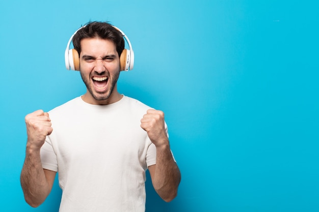 Young handsome man shouting aggressively with an angry expression or with fists clenched celebrating success