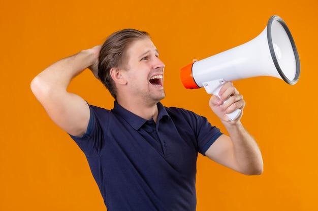 Молодой красивый мужчина, кричащий в мегафон, вышел и удивился, стоя на оранжевом фоне