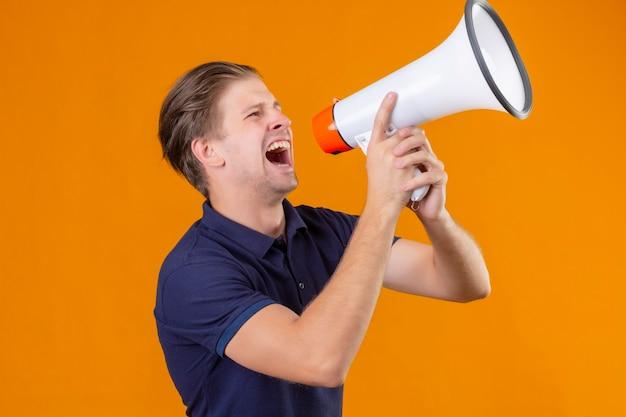 メガホンを通して叫んでいる若いハンサムな男が終了し、オレンジ色の背景の上に立って驚いた