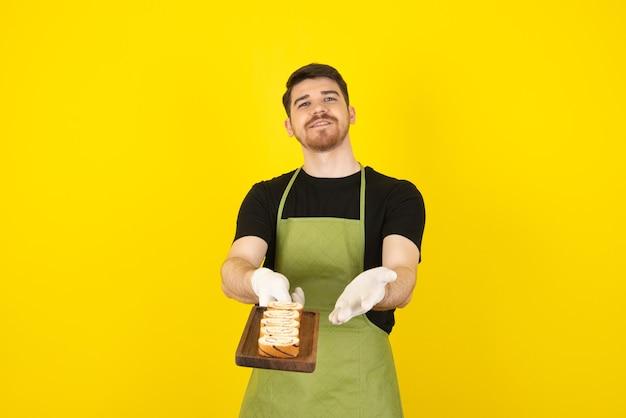 カメラに新鮮なケーキのスライスを示す若いハンサムな男。