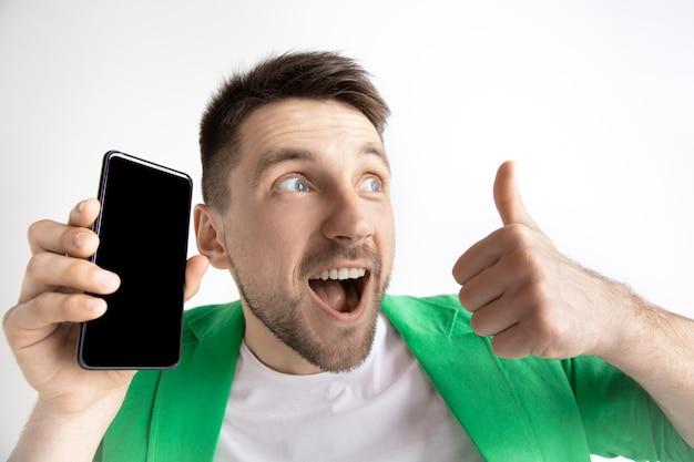 Молодой красавец показывает экран смартфона и подписывает знак ок, изолированные на сером фоне. человеческие эмоции, выражение лица, рекламная концепция.
