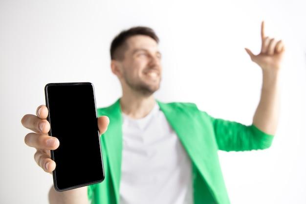 スマートフォンの画面を表示し、灰色の背景に分離されたokサインに署名する若いハンサムな男。人間の感情、顔の表情、広告のコンセプト。