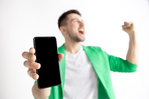 Молодой красавец показывает экран смартфона и подписывает знак ок, изолированный на сером