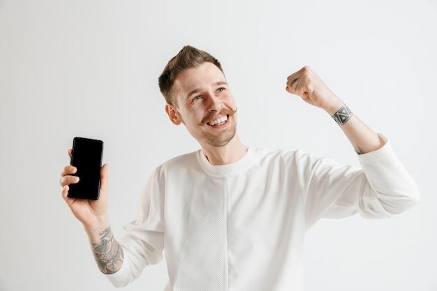 Giovane uomo bello che mostra lo schermo dello smartphone su grigio