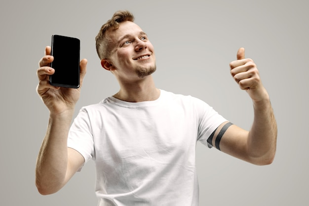 깜짝 얼굴로 충격에 회색 walll에 고립 된 스마트 폰 화면을 보여주는 젊은 잘 생긴 남자