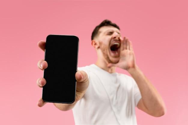 Молодой красавец показывает экран смартфона, изолированный на розовом фоне, в шоке от удивления