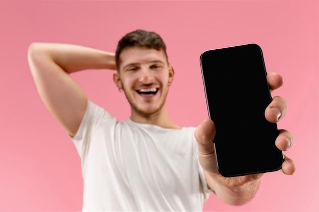 놀라운 충격에 분홍색 배경에 고립 된 스마트 폰 화면을 보여주는 젊은 잘 생긴 남자