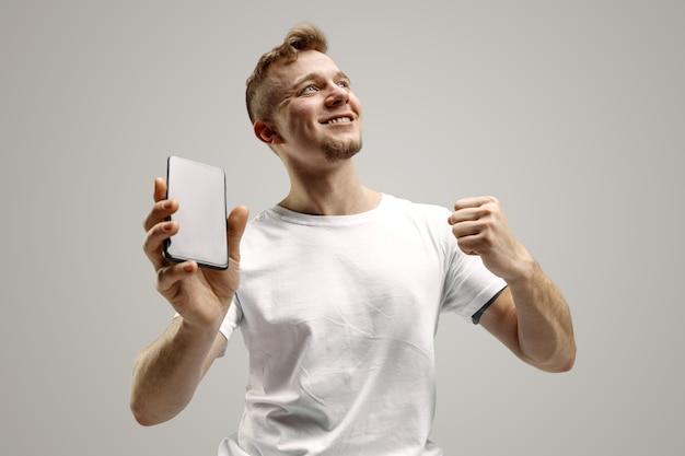 驚きの顔で灰色の背景にスマートフォンの画面を示す若いハンサムな男。人間の感情、表情の概念