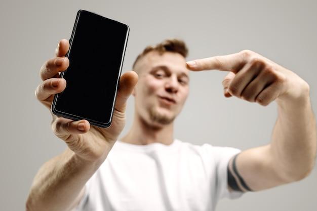 Молодой красавец показывает экран смартфона над серым пространством с удивленным лицом